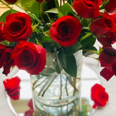 red roses in a glass vase with mirror