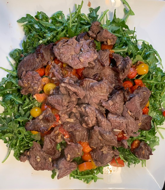 thinly sliced beef with arugula, tomatoes and pine nuts
