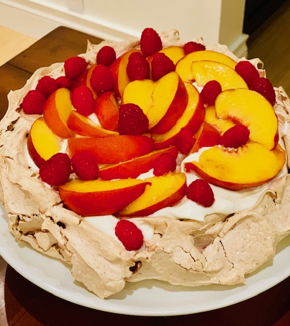 A Pavlova topped with Cream and Fresh Fruit